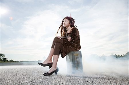 Girl sitting on suitcase Stock Photo - Premium Royalty-Free, Code: 6114-06597132