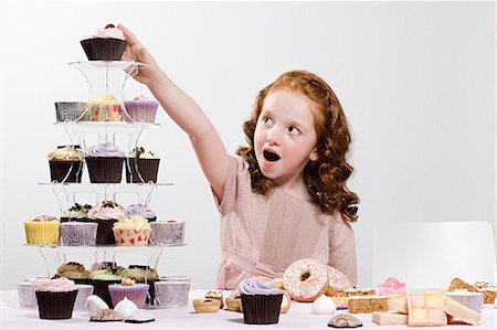Girl reaching for cake Stock Photo - Premium Royalty-Free, Code: 6114-06597754