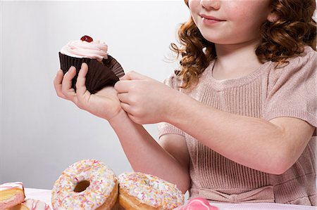 Girl with cupcake Stock Photo - Premium Royalty-Free, Code: 6114-06597717