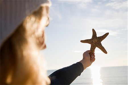 sea star - Woman holding up a starfish Stock Photo - Premium Royalty-Free, Code: 6114-06597849