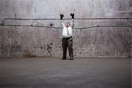 fat man full body - Man standing in warehouse Stock Photo - Premium Royalty-Free, Code: 6114-06598261