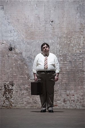 fat man full body - Man standing in warehouse Stock Photo - Premium Royalty-Free, Code: 6114-06598264