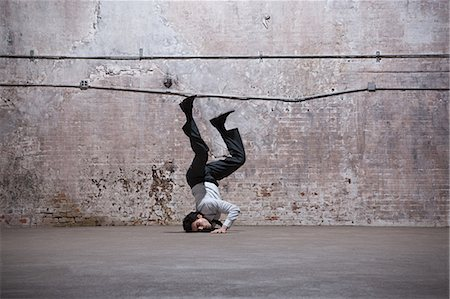 Man falling on head in warehouse Stock Photo - Premium Royalty-Free, Code: 6114-06598298