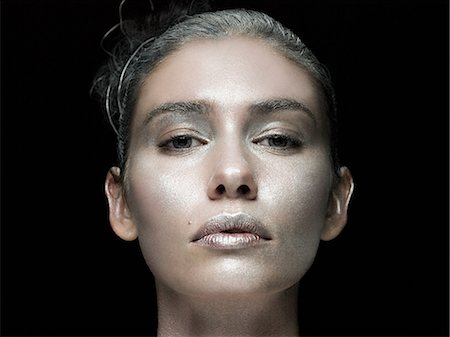shimmering - Young woman with face covered in silver make up Stock Photo - Premium Royalty-Free, Code: 6114-06598370
