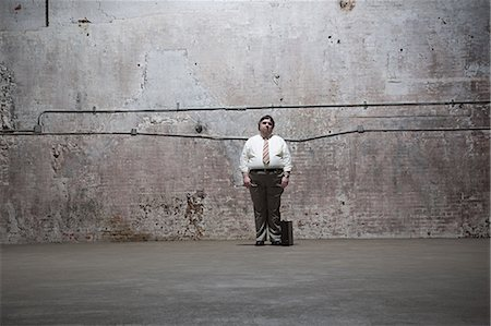 fat man full body - Man standing in warehouse Stock Photo - Premium Royalty-Free, Code: 6114-06598309
