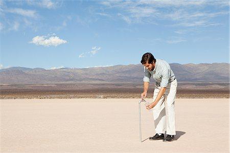 Man using facuet in desert landscape Stock Photo - Premium Royalty-Free, Code: 6114-06598943