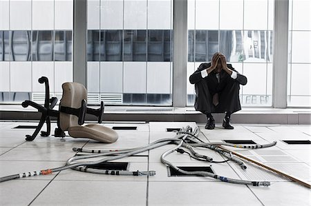Despairing businessman in abandoned office Stock Photo - Premium Royalty-Free, Code: 6114-06599412