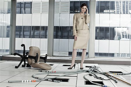 Businesswoman in abandoned office Stock Photo - Premium Royalty-Free, Code: 6114-06599417