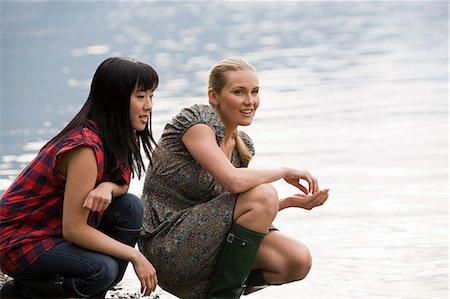 Two young women crouching near lake Stock Photo - Premium Royalty-Free, Code: 6114-06599765