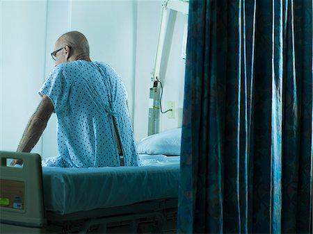 Senior man sitting on hospital bed Stock Photo - Premium Royalty-Free, Code: 6114-06599956