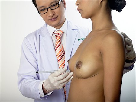 Cosmetic surgeon marking womans breasts Stock Photo - Premium Royalty-Free, Code: 6114-06646584