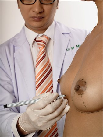 Cosmetic surgeon marking womans breasts Stock Photo - Premium Royalty-Free, Code: 6114-06646603