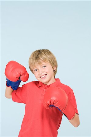 Boy wearing boxing gloves Stock Photo - Premium Royalty-Free, Code: 6114-06651049