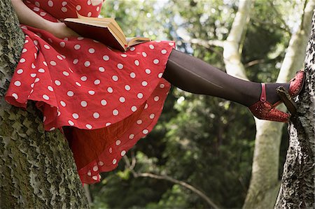 Woman reading a book in a tree Stock Photo - Premium Royalty-Free, Code: 6114-06653767