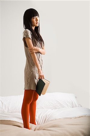Young woman on bed with book Stock Photo - Premium Royalty-Free, Code: 6114-06653930