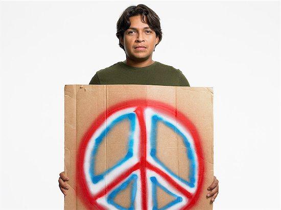 Man holding peace sign Stock Photo - Premium Royalty-Free, Image code: 6114-06655865