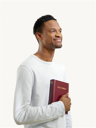 Smiling man holding a bible Stock Photo - Premium Royalty-Free, Code: 6114-06657839