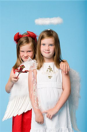 Twin girls dressed as an angel and devil Stock Photo - Premium Royalty-Free, Code: 6114-06659755
