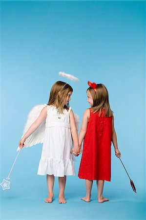 Twin girls dressed as an angel and devil Stock Photo - Premium Royalty-Free, Code: 6114-06659779