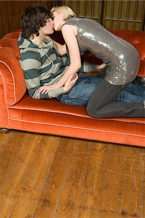 Teenagers kissing on a sofa Stock Photo - Premium Royalty-Free, Code: 6114-06660843