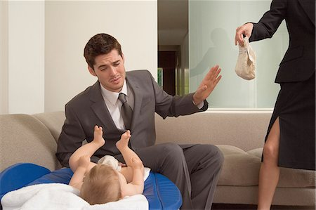 Business couple changing baby's nappy Stock Photo - Premium Royalty-Free, Code: 6114-06663169