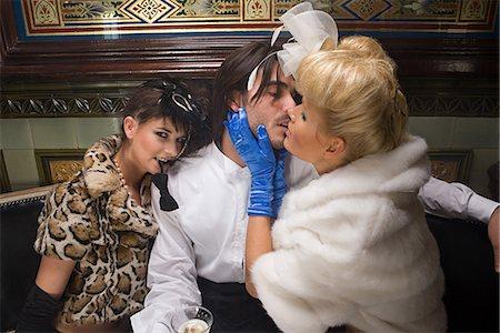 dominant woman - Two lavishly dressed women flirting with a man Stock Photo - Premium Royalty-Free, Code: 6114-06671837