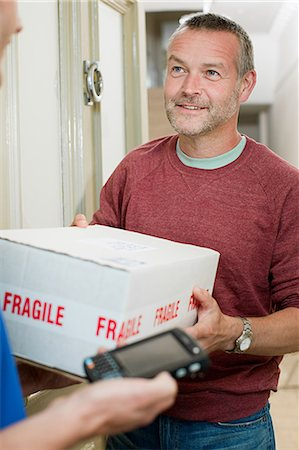 fragile - Delivery man delivering parcel Stock Photo - Premium Royalty-Free, Code: 6114-06600152