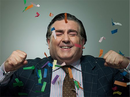 Mature businessman with ticker tape, portrait Stock Photo - Premium Royalty-Free, Code: 6114-06600171