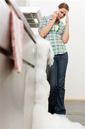 Young woman on phone with overflowing dishwasher Stock Photo - Premium Royalty-Free, Code: 6114-06600269
