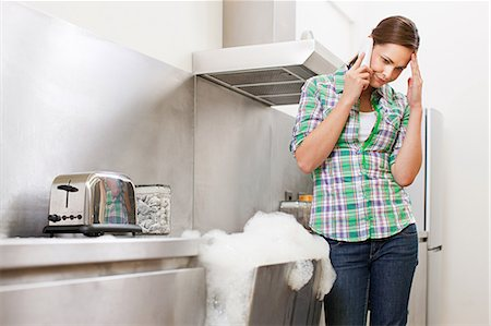 Young woman on phone with overflowing dishwasher Stock Photo - Premium Royalty-Free, Code: 6114-06600270