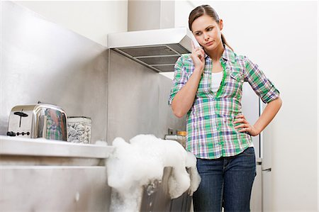 Young woman on phone with overflowing dishwasher Stock Photo - Premium Royalty-Free, Code: 6114-06600271