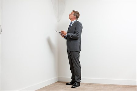 Mature man examining damp patch on wall Stock Photo - Premium Royalty-Free, Code: 6114-06600301