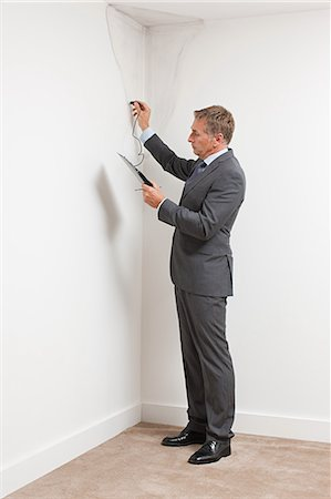 Mature man examining damp patch on wall Stock Photo - Premium Royalty-Free, Code: 6114-06600302