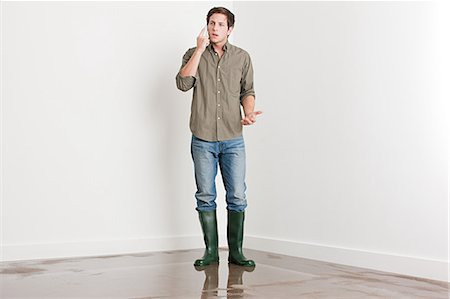 Young man on flooded floor Stock Photo - Premium Royalty-Free, Code: 6114-06600317
