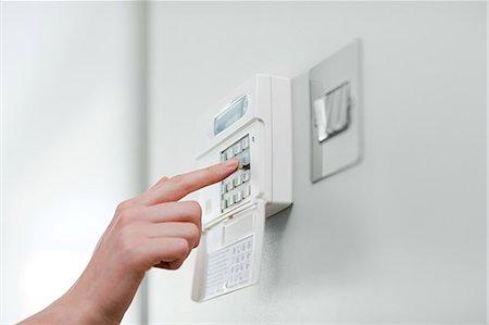 Woman setting burglar alarm Stock Photo - Premium Royalty-Free, Code: 6114-06600330