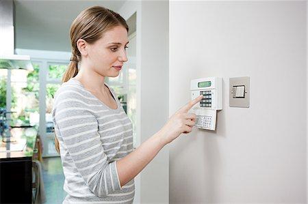 Woman setting burglar alarm Stock Photo - Premium Royalty-Free, Code: 6114-06600332