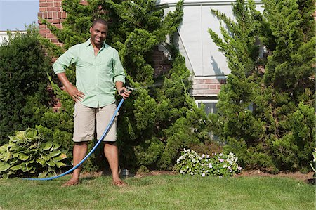 Man watering grass with hosepipe Stock Photo - Premium Royalty-Free, Code: 6114-06600449