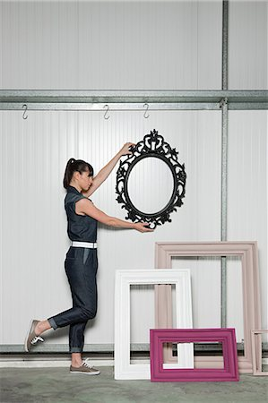 Young woman positioning picture frame Stock Photo - Premium Royalty-Free, Code: 6114-06600485