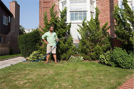 Man watering grass with hosepipe Stock Photo - Premium Royalty-Free, Code: 6114-06600430