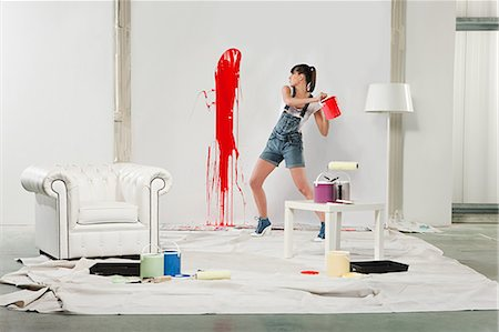 red chair - Young woman splashing red paint on white wall Stock Photo - Premium Royalty-Free, Code: 6114-06600542