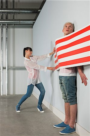 funny looking people - Young woman trapping young man behind striped wallpaper Stock Photo - Premium Royalty-Free, Code: 6114-06600546