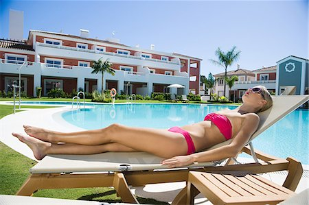Woman sunbathing on sunlounger at poolside Stock Photo - Premium Royalty-Free, Code: 6114-06600594