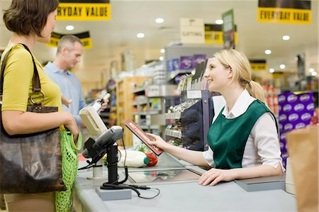 Cashier and customers at supermarket checkout Stock Photo - Premium Royalty-Free, Code: 6114-06600657