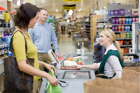 Cashier and customers at supermarket checkout Stock Photo - Premium Royalty-Free, Code: 6114-06600655