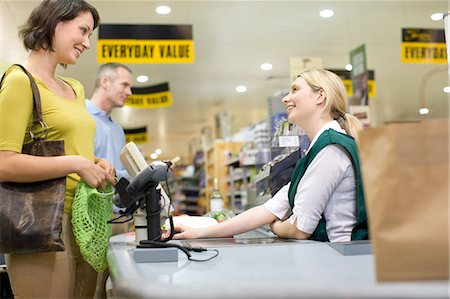 Cashier and customers at supermarket checkout Stock Photo - Premium Royalty-Free, Code: 6114-06600656