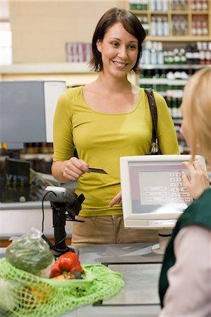 Woman at supermarket checkout Stock Photo - Premium Royalty-Free, Code: 6114-06600662