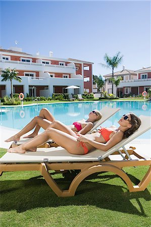 Two women sunbathing on sunloungers at poolside Stock Photo - Premium Royalty-Free, Code: 6114-06600601