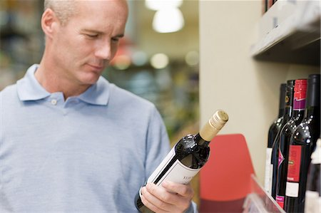 selecting - Man choosing wine in supermarket Stock Photo - Premium Royalty-Free, Code: 6114-06600711