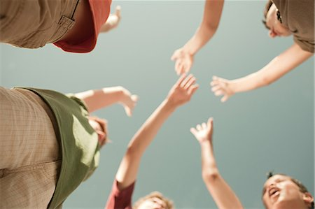 Boys doing high five, low angle view Stock Photo - Premium Royalty-Free, Code: 6114-06600840