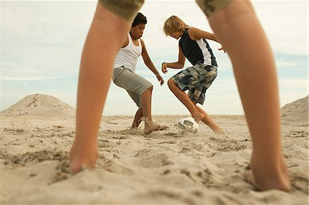 Boys playing football on beach Stock Photo - Premium Royalty-Free, Code: 6114-06600845